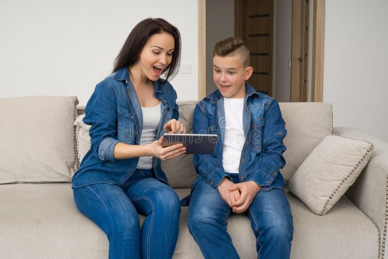 Lyckligt familjsammanträde på soffan och använda den digitala minnestavlan hemma arkivbild