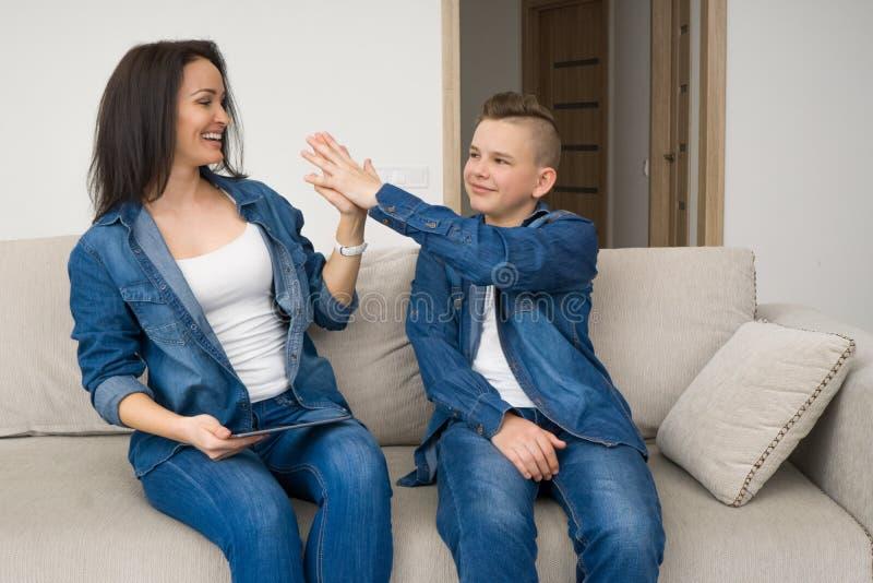 Lyckligt familjsammanträde på soffan och använda den digitala minnestavlan hemma arkivbilder