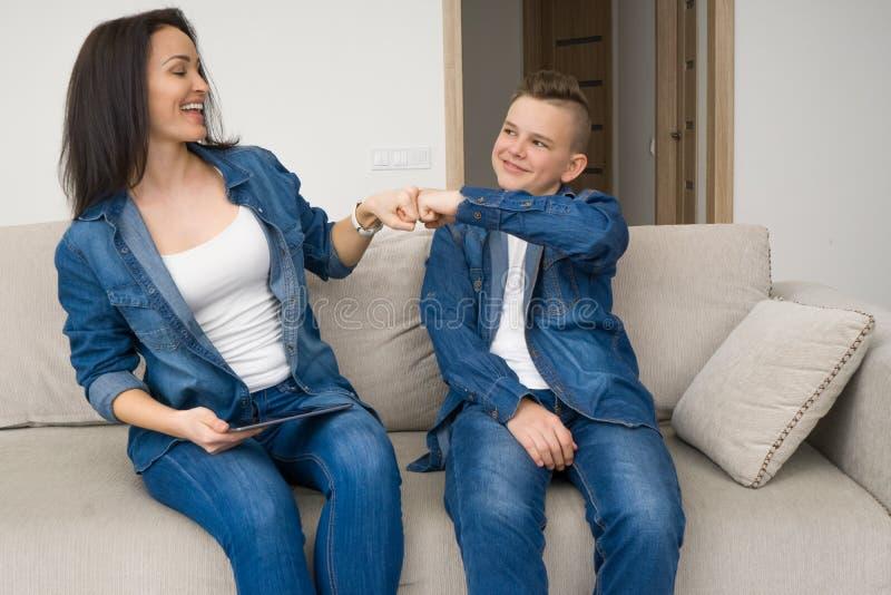 Lyckligt familjsammanträde på soffan och använda den digitala minnestavlan hemma arkivfoto