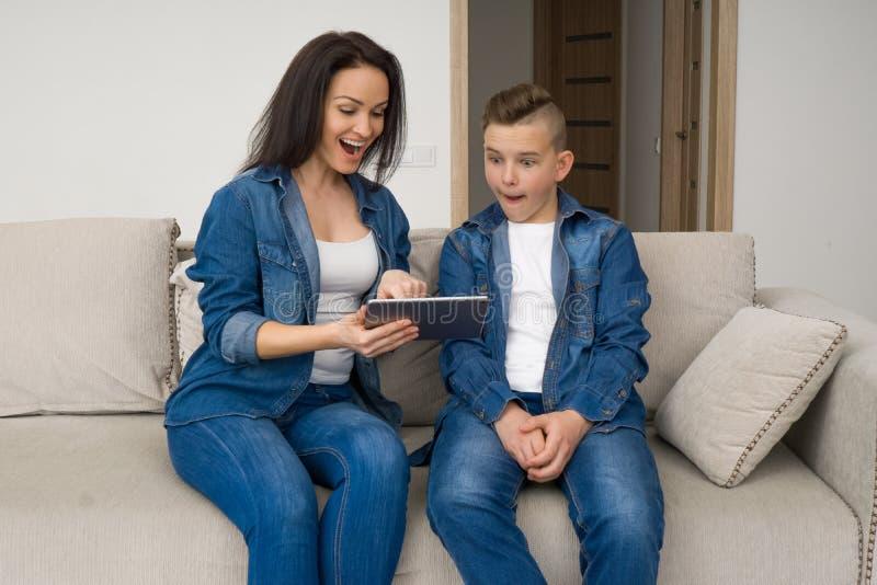 Lyckligt familjsammanträde på soffan och använda den digitala minnestavlan hemma arkivfoton