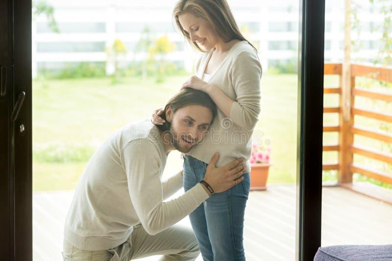 Lyckligt farsa-till-var sätter örat till den gravida buken, havandeskap och män royaltyfria bilder