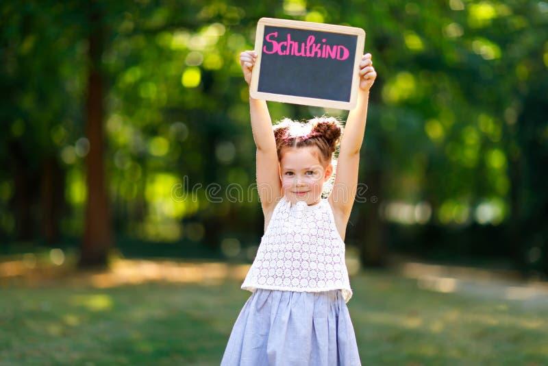 Lyckligt flickaanseende f?r liten unge med skrivbordet och ryggs?ck eller axelv?ska Skolbarn p? den f?rsta dagen av element?r gru arkivbilder