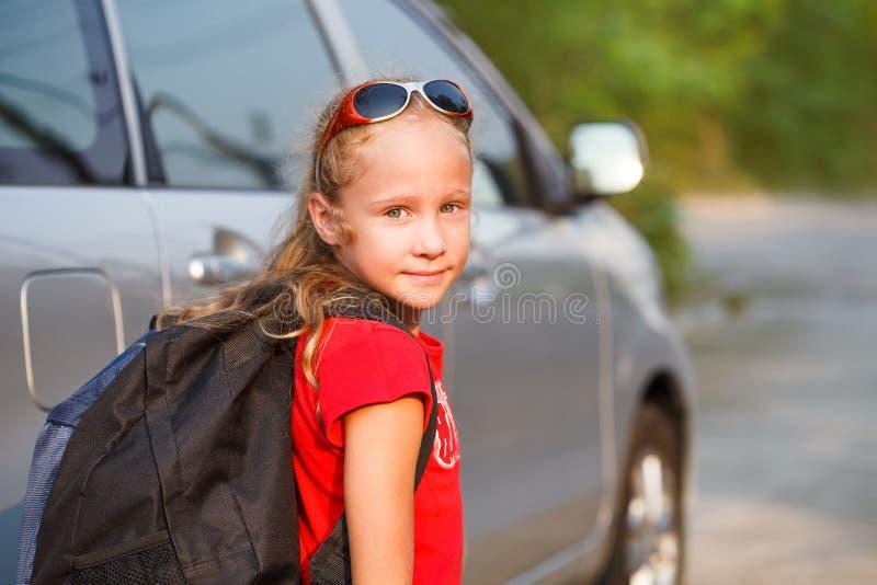 Lyckligt flickaanseende nära bilen arkivbild
