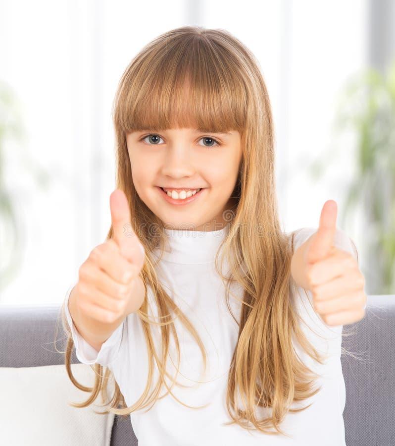 Lyckligt   flickan visar upp tummar royaltyfria bilder