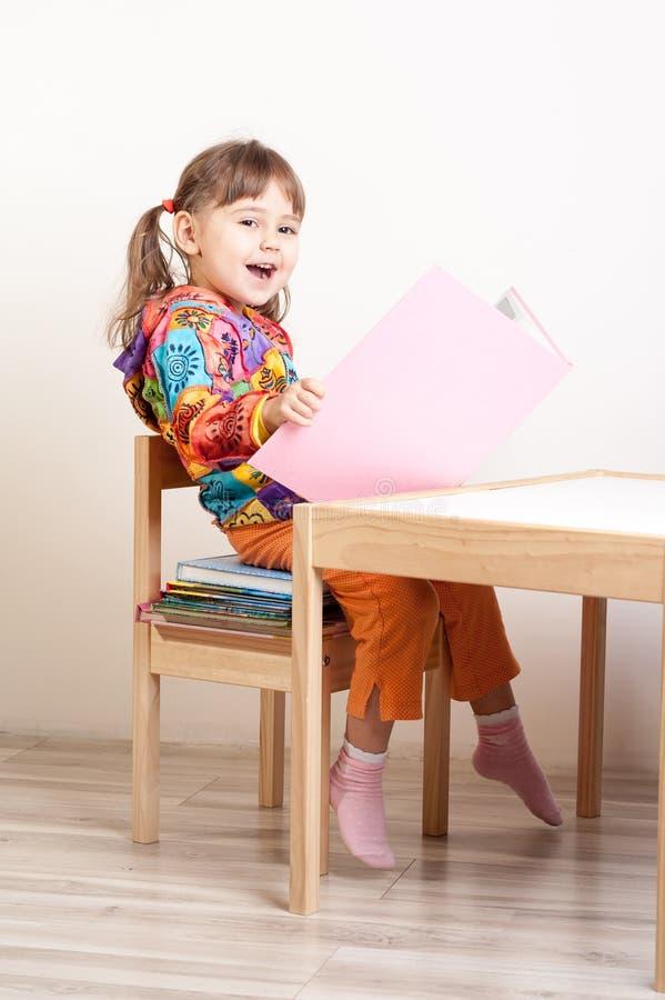 Lyckligt flickasammanträde på bunt av böcker på skrivbordet arkivbilder