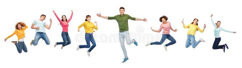 Lyckligt folk eller vänner som hoppar i luft över vit royaltyfri foto