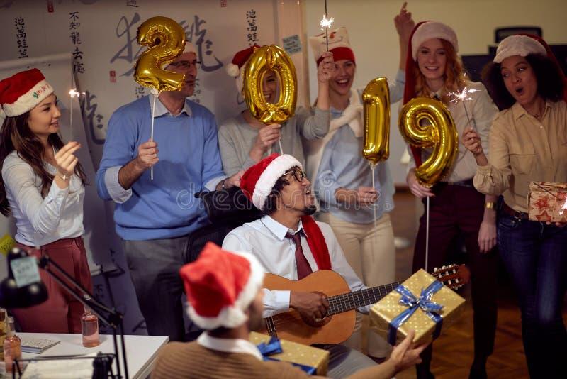 Lyckligt folk för affärsgrupp i jultomtenhatten som har gyckel för kändisjulparti royaltyfria bilder