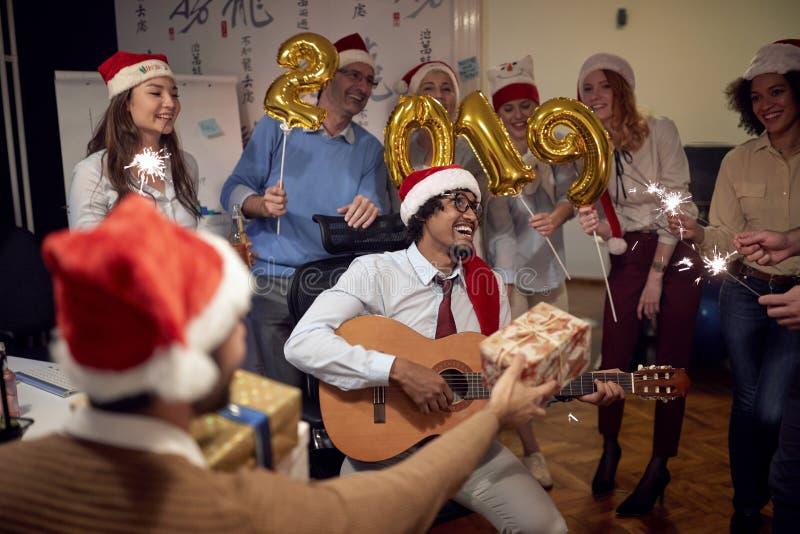 Lyckligt folk för affärsgrupp i jultomtenhatten som har gyckel för kändisjulparti med sång royaltyfria bilder