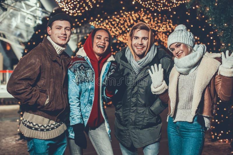 Lyckligt folk i varm kläder som framme poserar för foto av belysning royaltyfri fotografi
