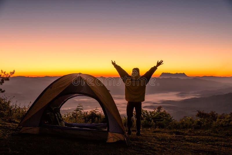 Lyckligt folk med armar som är öppna nära tälten runt om bergen royaltyfria foton