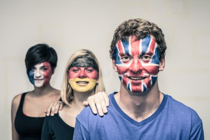 Lyckligt folk med européflaggor på framsidor royaltyfria foton