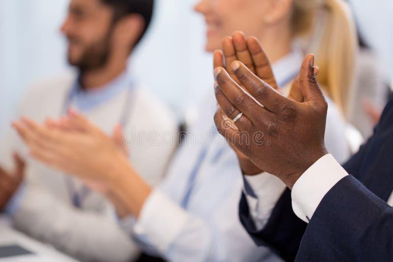 Lyckligt folk som applåderar på affärskonferensen arkivbilder