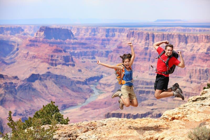 Lyckligt folk som hoppar i grand Canyon fotografering för bildbyråer
