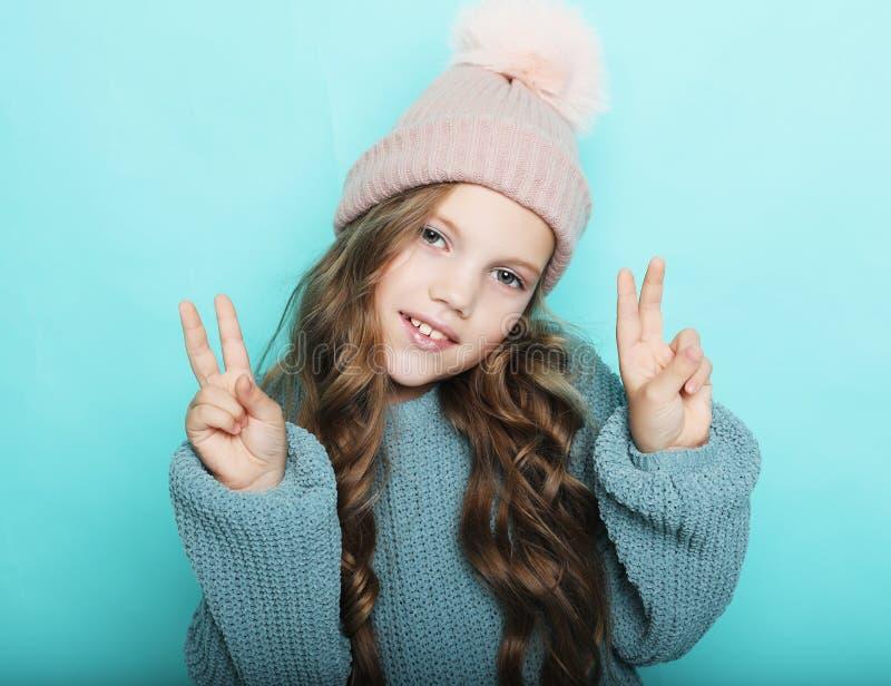 Lyckligt folkbegrepp - le lilla flickan som visar fredgest med fingrar över blå bakgrund arkivfoto