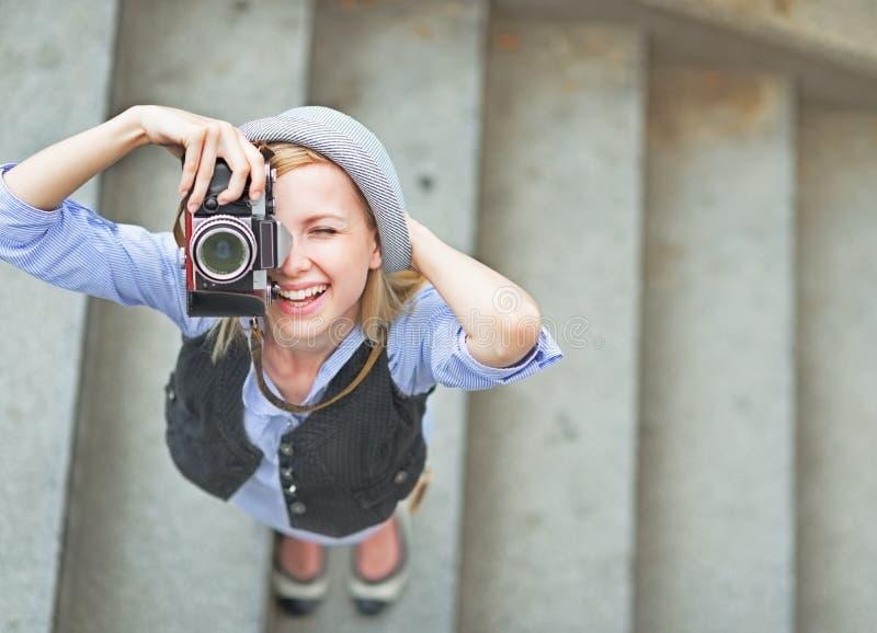 Lyckligt foto för hipsterflickadanande med den retro kameran på stadsgatan arkivfoto