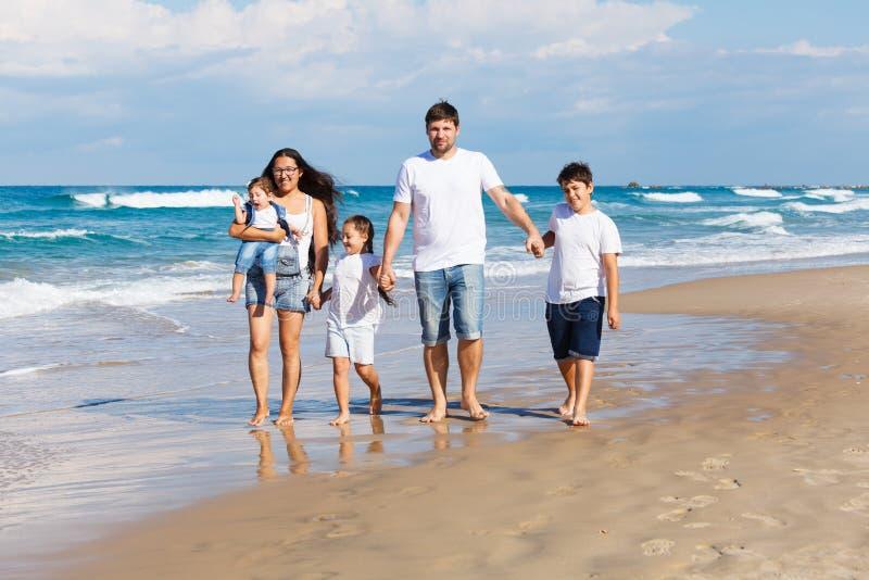 lyckligt gå för strandfamilj arkivfoto