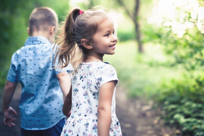 Lyckligt gå för ungar som är utomhus- på, parkerar hållen deras händer royaltyfria foton
