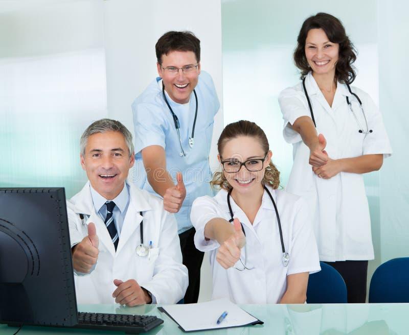 Lyckligt ge sig för medicinskt lag tummar upp arkivbilder