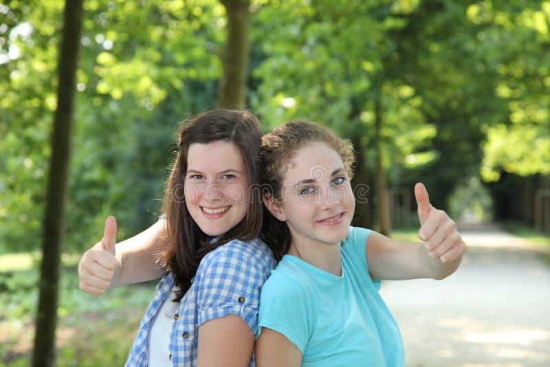Lyckligt ge sig för tonårs- flickor tummar upp royaltyfria bilder
