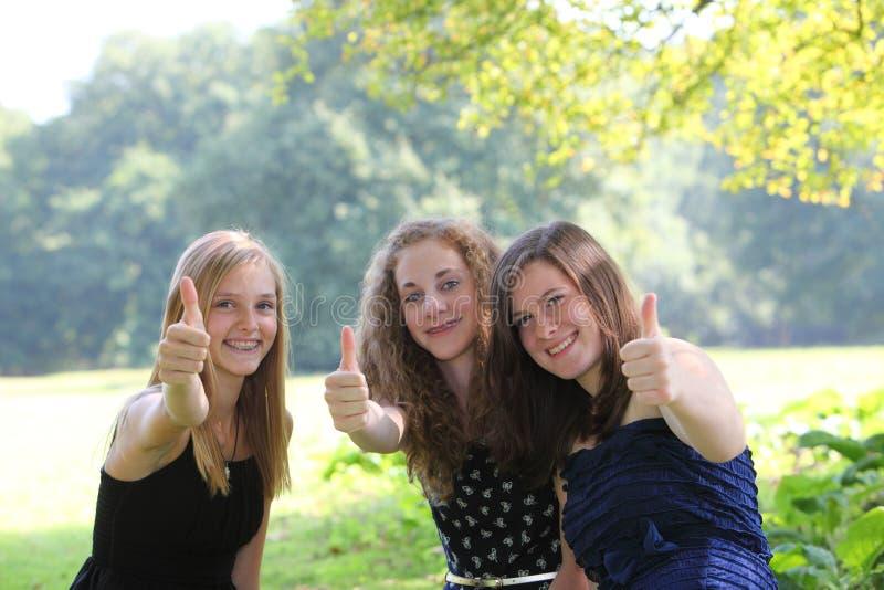 Lyckligt ge sig för tonårs- flickor tummar upp royaltyfri bild