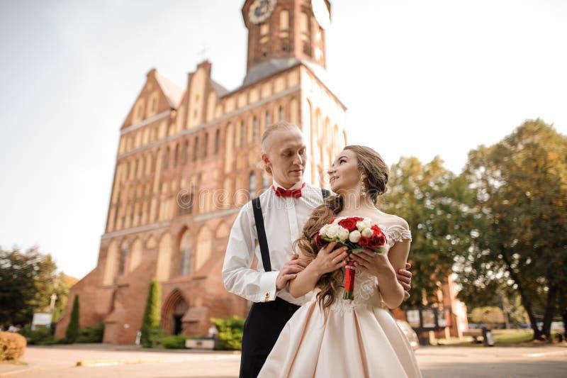 Lyckligt gift par med en gifta sig bukett som står i bakgrund av härlig byggnad royaltyfria bilder