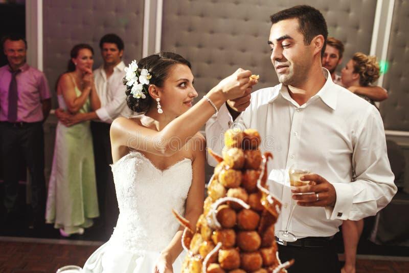Lyckligt gift par som äter den läckra chokladbröllopstårtan på royaltyfri fotografi