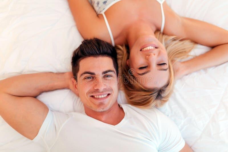 Lyckligt gift par som kopplar av att ligga på säng royaltyfri bild