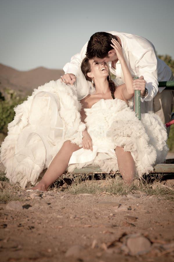Lyckligt gifta sig nyligen parsammanträde på runda om lekplats arkivfoto