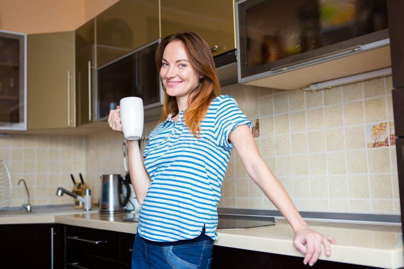Lyckligt gladlynt gulligt ungt gravid kvinnaanseende på kök arkivfoto