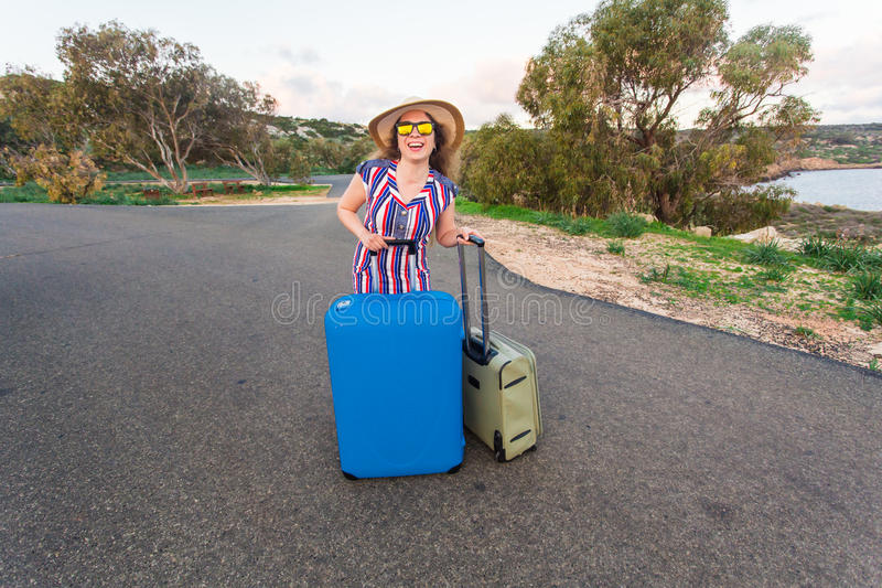Lyckligt gladlynt handelsresandekvinnaanseende med resväskor på vägen och le Begrepp av loppet, ferier, resa royaltyfri bild
