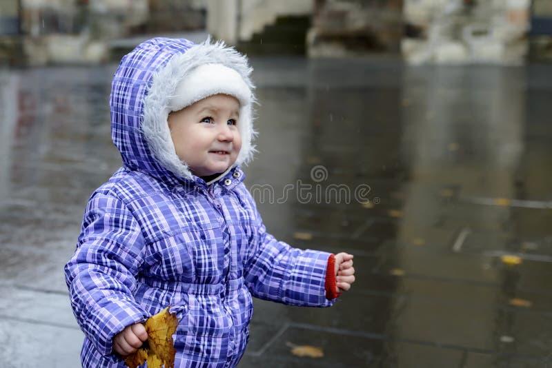 Lyckligt glat barn som rymmer ett höstblad, i händer och att le arkivbilder