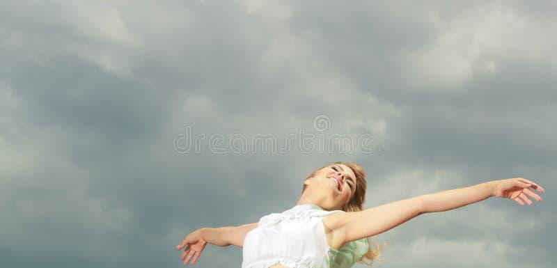 Lyckligt glat för kvinna med armar upp mot himmel royaltyfri fotografi