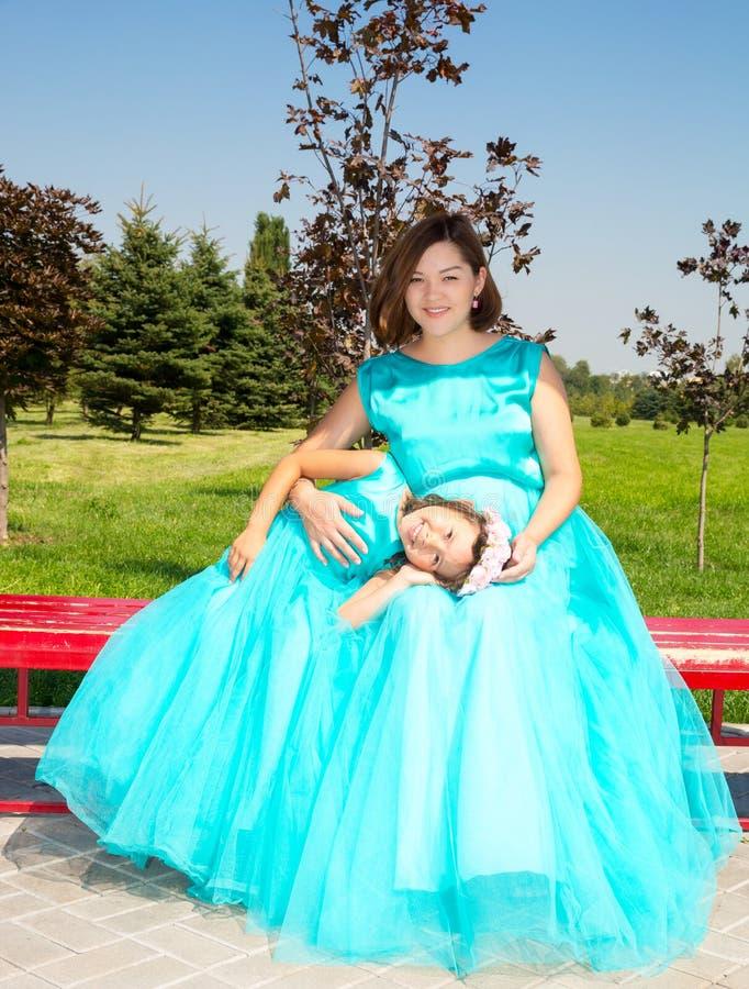 Lyckligt gravid asiatiskt krama för mamma- och barnflicka Begreppet av barndom och familjen Den härliga modern och hon behandla s arkivbild