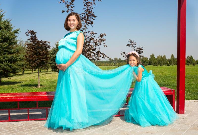 Lyckligt gravid asiatiskt krama för mamma- och barnflicka Begreppet av barndom och familjen Den härliga modern och hon behandla s arkivbilder