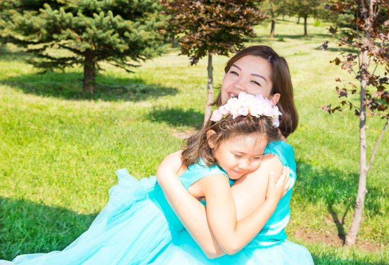 Lyckligt gravid asiatiskt krama för mamma- och barnflicka Begreppet av barndom och familjen Den härliga modern och hon behandla s arkivfoton