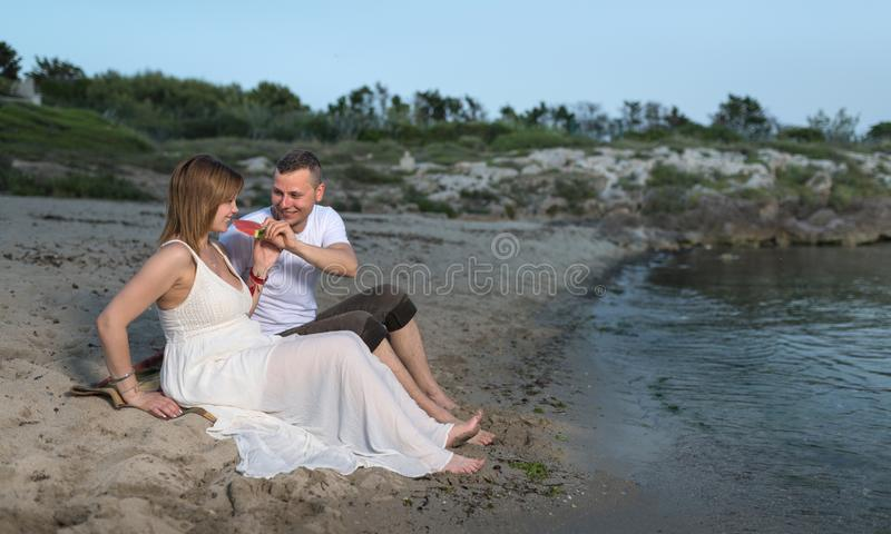lyckligt gravid avslappnande barn f?r strandpar royaltyfri bild