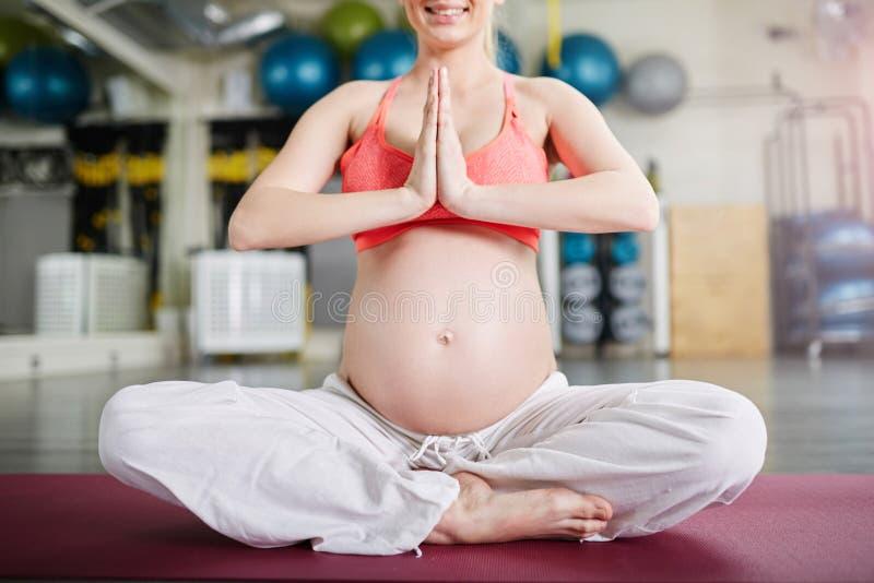 Lyckligt gravid kvinnasammanträde i lotusblomma poserar vikning henne händer royaltyfria bilder