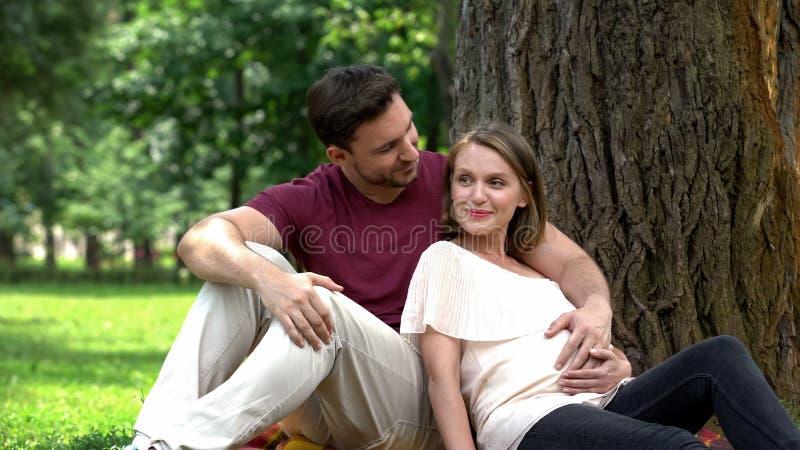 Lyckligt gravid parsammanträde parkerar in, planläggningen säkrat familjeliv, välfärd arkivbilder