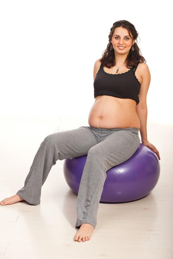 Lyckligt gravid sitter på konditionboll arkivbild