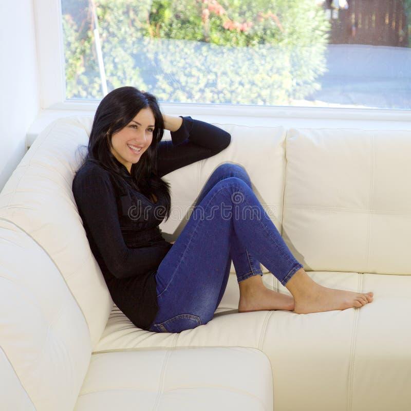 Lyckligt gulligt sammanträde för ung kvinna på att le för soffa arkivfoto