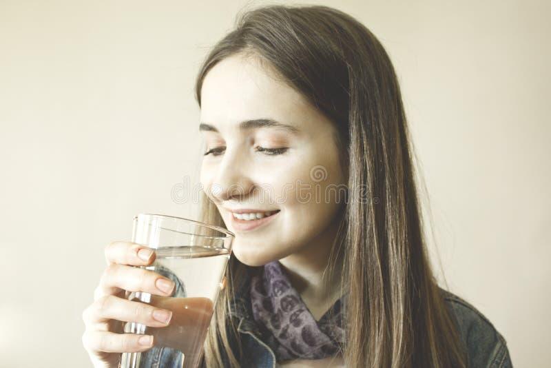 Lyckligt härligt dricksvatten för ung kvinna royaltyfri foto