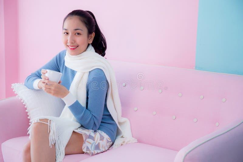 Lyckligt härligt för kaffekopp för ung kvinna hållande sammanträde för halsduk bärande på signal för pastellfärgad färg för varda royaltyfri fotografi