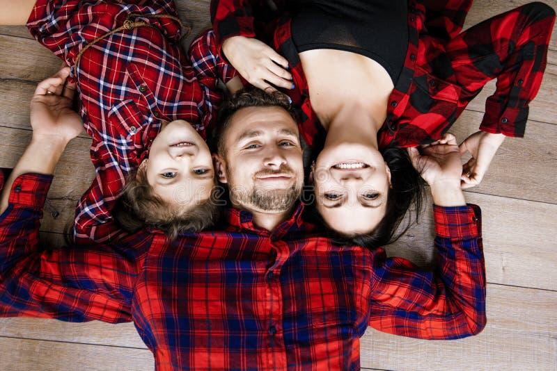 Lyckligt härligt lyckligt hemmastatt ligga för familj tillsammans på wooden royaltyfria foton