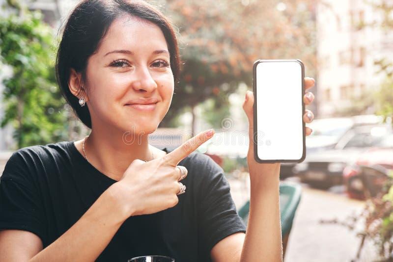 Lyckligt härligt kvinnainnehav och visningmobiltelefon med den tomma vita skärmen i kafé royaltyfri fotografi