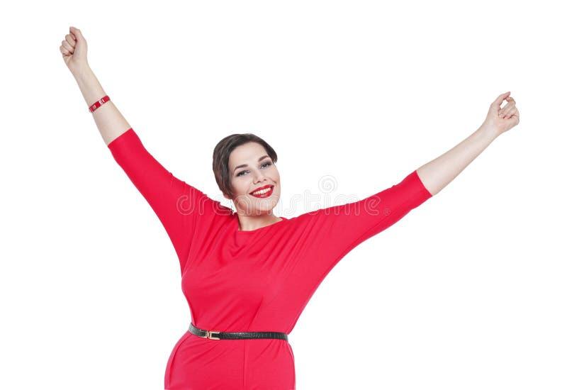 Lyckligt härligt plus formatkvinna i röd klänning med händer up isola arkivbild