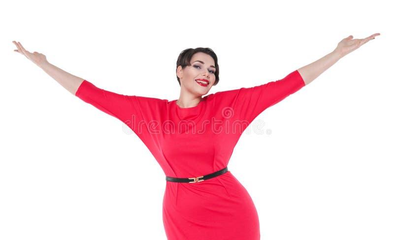 Lyckligt härligt plus formatkvinna i röd klänning med händer up isolator arkivbilder
