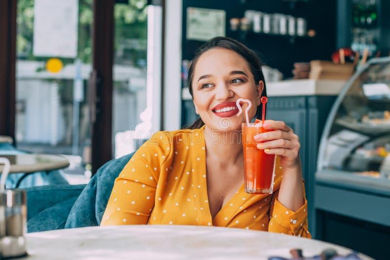 Lyckligt härligt plus formatkvinnan som ler och dricker den sunda morotsmoothien i kafé arkivbilder