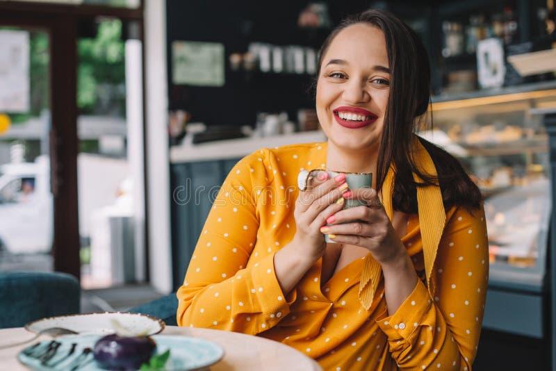 Lyckligt härligt plus formatkvinnan som ler och dricker kaffe i kafé royaltyfria foton