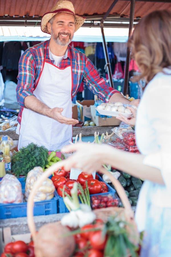 Lyckligt högt bondeanseende bak stånd som säljer organiska grönsaker royaltyfri bild
