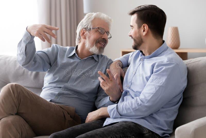 Lyckligt h?gt fadersamtal som kopplar av p? soffan med den millennial sonen arkivbilder